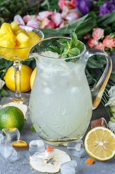 Летом свежие прохладительные напитки. ледяной лимонад в кувшине и лимоны и апельсин с мятой на столе открытый.