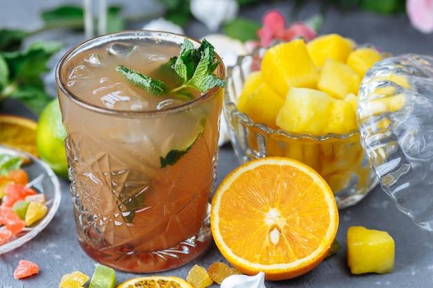 Холодный освежающий ананасный коктейль с лаймом и мятой для жаркого летнего дня на сером фоне, украшенный цукатами, кубиками мяты и ананаса.