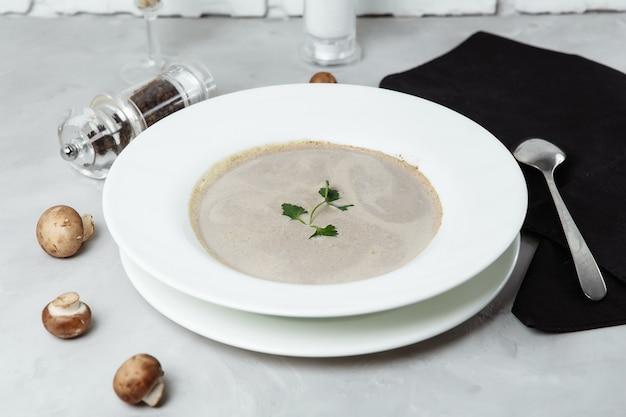 灰色の背景にパセリとキノコのスープ