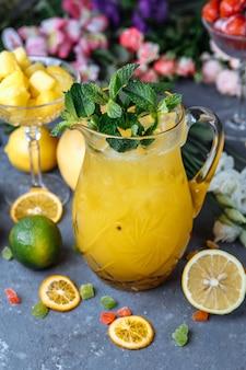 Летом свежие прохладительные напитки. ледяной лимонад в кувшине и лимоны и апельсин с мятой на столе открытый. апельсиновый лимонад в кувшине