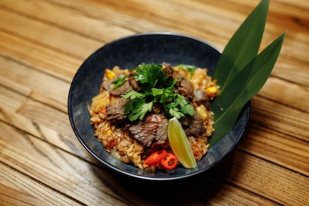 Жареный рис с говядиной и овощами на деревянном фоне