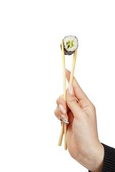 Рука держит суши роллы с палочками для еды