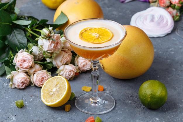 Апельсиновый коктейль с ломтиком апельсина на черном бетонном столе. концепция летнего коктейля с декором