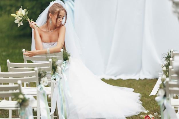 路上の緑の中でポーズをとって壮大なウェディングドレスの美しい花嫁。広告ドレスの花嫁のコンセプト
