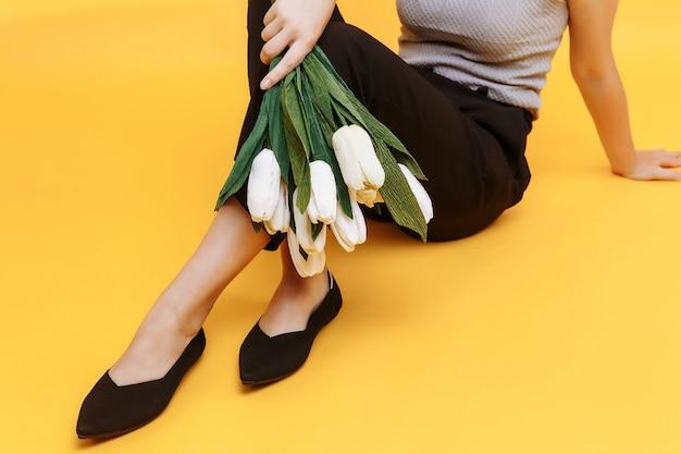 Красивые женские ножки одеты в стильные черные плоские туфли. черные сандалии