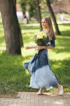 日当たりの良い春の公園でドレスでポーズをとるスタイリッシュな女の子。春に花束を持って立っている美しい少女の穏やかな肖像画。