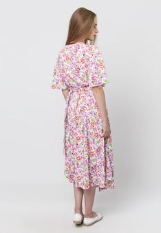 明るい空間で、明るい夏のドレスを着たエレガントな少女の完全な長さ。衣料品店の広告コンセプト。ソーシャルネットワークとバナーのコンテンツ。