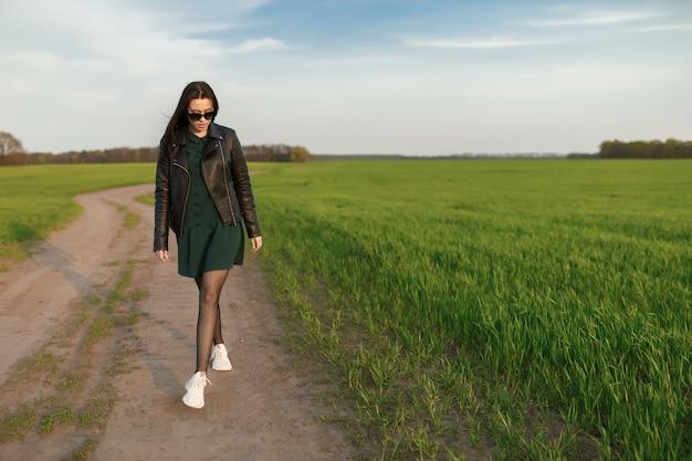 緑の野原を歩いているスタイリッシュな女性の完全な長さの肖像画。若い笑顔の女性が自然の中歩いています。緑の春の牧草地