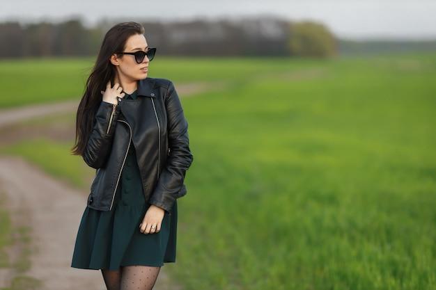 の野原を歩いているスタイリッシュな女性の肖像画。若い笑顔の女性が自然の中歩いています。緑の春の牧草地