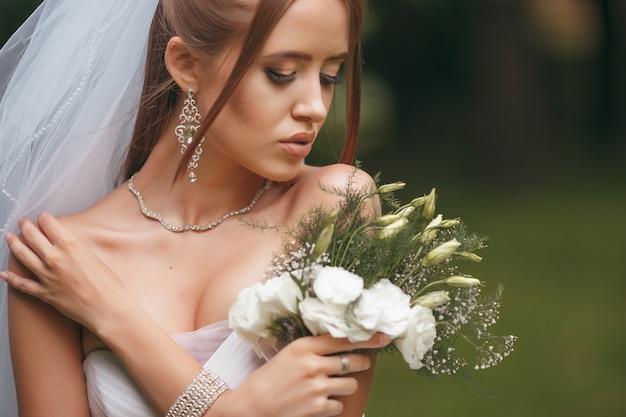 Красивая невеста в пышном свадебном платье позирует среди зелени на улице. двушка позирует в свадебном платье для рекламы. концепция невесты для рекламы платьев