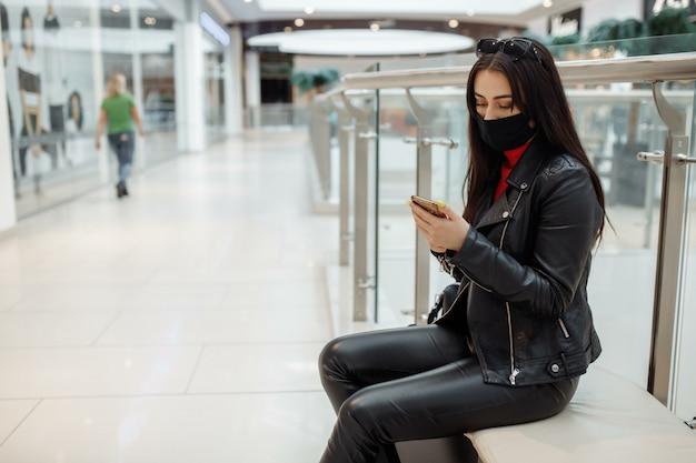 医療の黒いマスクとショッピングセンターでの携帯電話を持つ女性。コロナウイルスパンデミック。マスクを持つ女性がショッピングセンターに立っています。