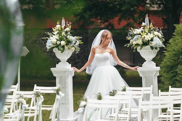 路上の緑に囲まれたポーズ壮大なウェディングドレスの美しい花嫁。女性は広告のためのウェディングドレスでポーズします。広告ドレスの花嫁のコンセプト
