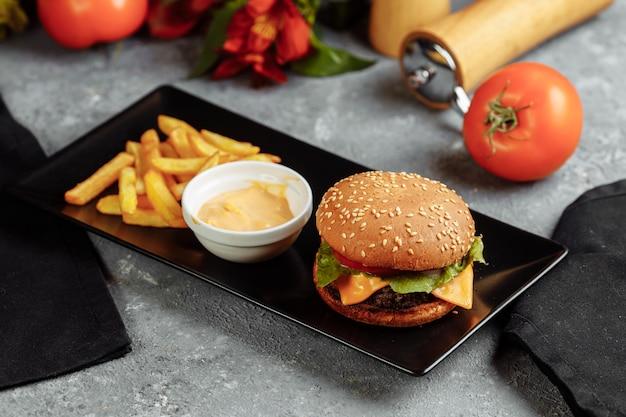 Бургер с котлетой, сыром и помидорами. с картофелем фри и гамбургерным соусом