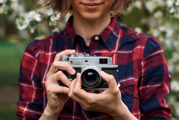 Женщина с ретро камерой, принимая фото на открытом воздухе