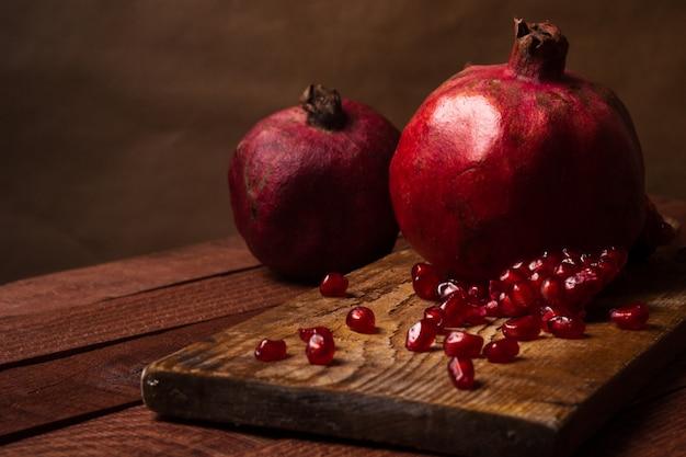 木製のテーブルの種子とザクロ
