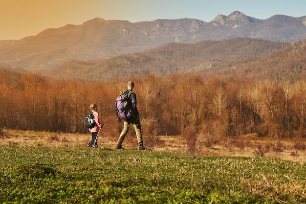 Счастливый отец и маленький сын гуляют в горах.
