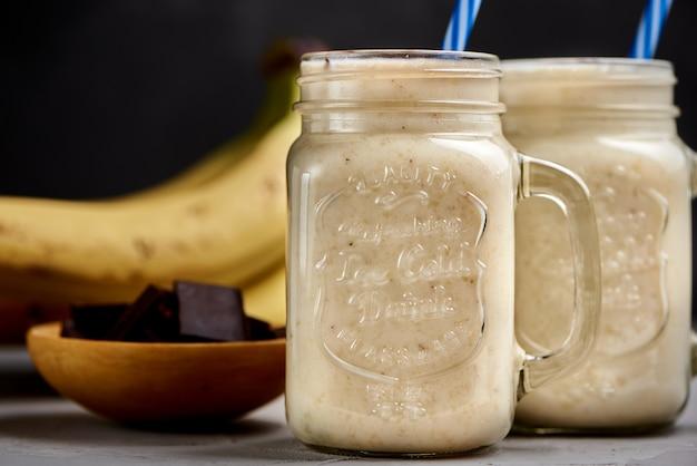 Банановый молочный коктейль в стакане с шоколадом на серой бетонной поверхности, крупным планом