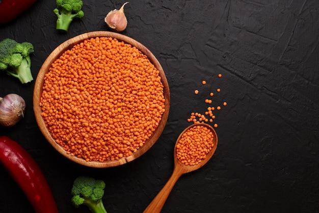 健康食品、ダイエット、ビーガンタンパク質源のコンセプト。マメ科植物、赤レンズ豆の生。トップビューフラット横たわっていた。テキストの空き容量。