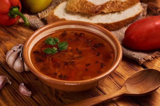 木製のテーブルに伝統的なスープボルシチのボウル。