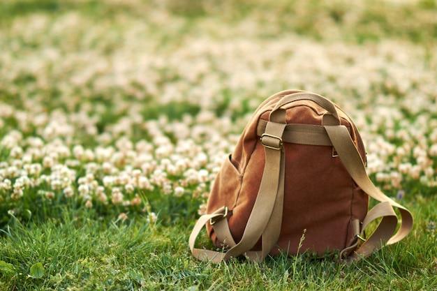 Коричневый рюкзак на фоне зеленой травы и цветы на фоне. выборочный фокус.