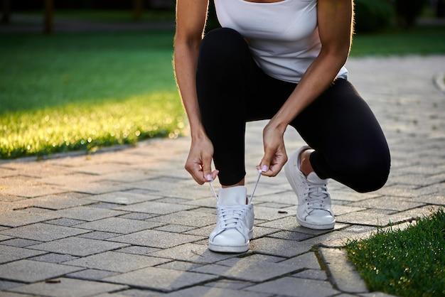 Молодая женщина завязывает шнурки перед бегом