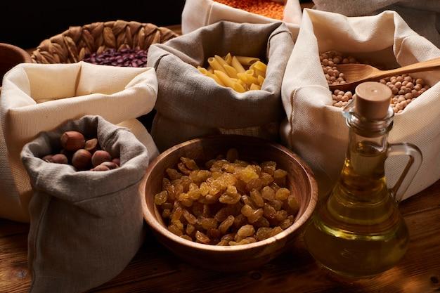 ナッツ、ドライフルーツ、マカロン、割りのエココットンバッグ、ガラスの瓶、キッチンの木製テーブル