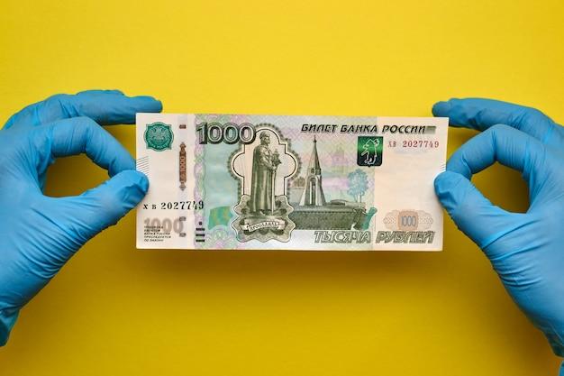 Руки в перчатках держат банкноту