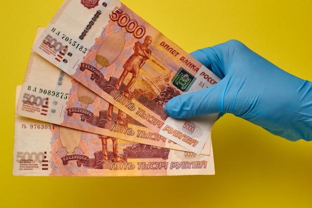 Руки в перчатках держат банкноты