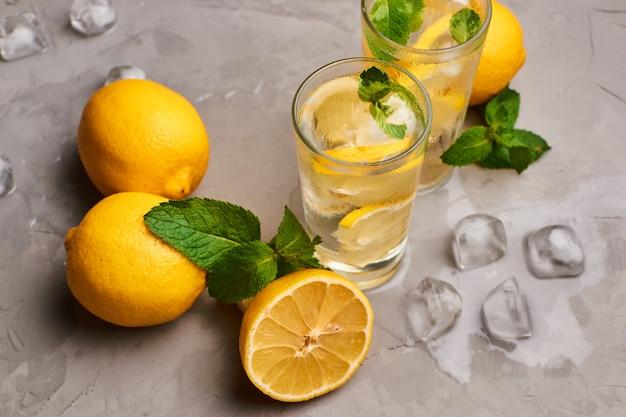いくつかの丸ごとのレモン、新鮮なミントの葉、灰色のコンクリートの表面、暗い背景に氷のかけらに囲まれたレモンスライスのある純粋な水で満たされたグラス。
