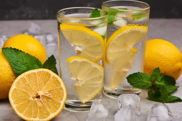 Стаканы наполнены чистой водой с кусочками лимона в окружении нескольких целых лимонов, свежих листьев мяты и кусочков льда на серой бетонной поверхности, темный фон.