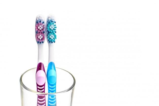ガラスにカラフルな歯ブラシ。口腔衛生のコンセプトです。白色の背景。