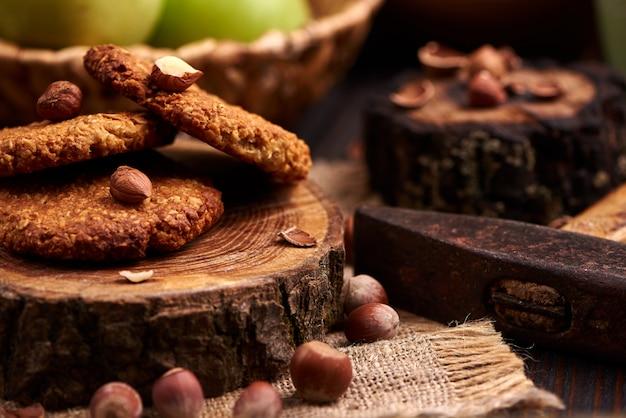 木製の背景にヘーゼルナッツと自家製オートミールクッキー