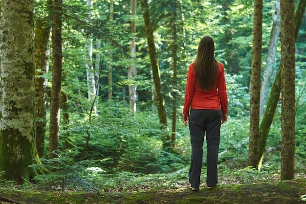 Женщина стоит в уютном лесу без дороги. затерянный в лесу.