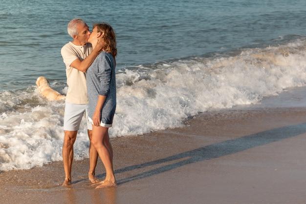 Счастливая зрелая пара целуется на пляже