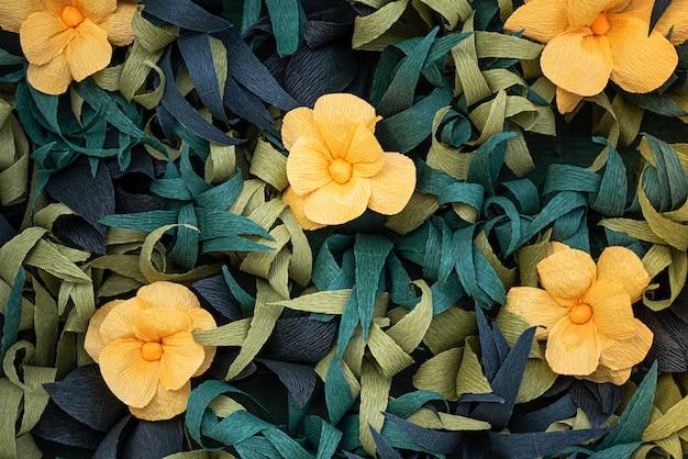 Желтые бумажные цветы среди зеленых листьев