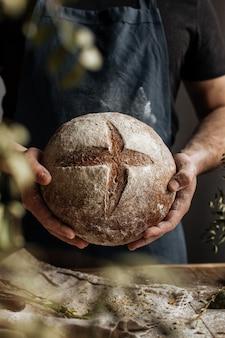 Руки пекаря держат буханку ржаного хлеба над деревянным столом.