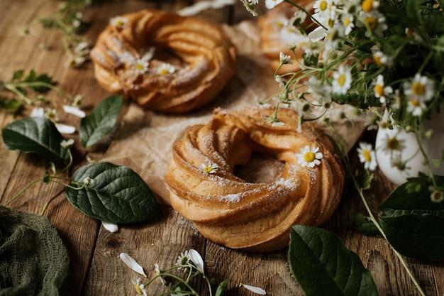 Кремовые слоеные кольца на деревянном фоне среди цветов ромашки.