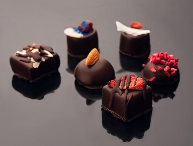 Шоколадные конфеты без сахара на черном акриле. сырые веганские шоколадные конфеты.