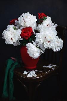 Белые пионы и красные розы в красной вазе на деревянном стуле.