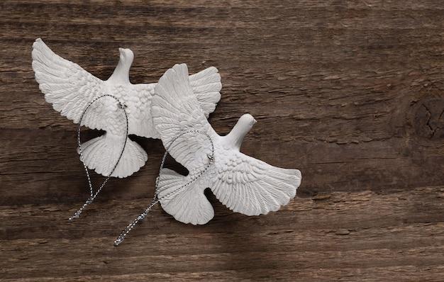 Черепаховые голуби на деревянной доске. каждый голубь-черепаха запутанно лепится из ремесленного материала из смолы, чтобы выглядеть реалистично, как настоящие голуби.