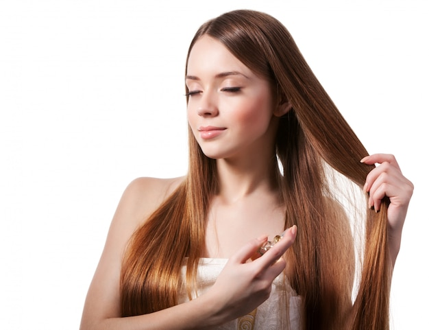 Девушка с каштановыми волосами распыляет духи на запястье