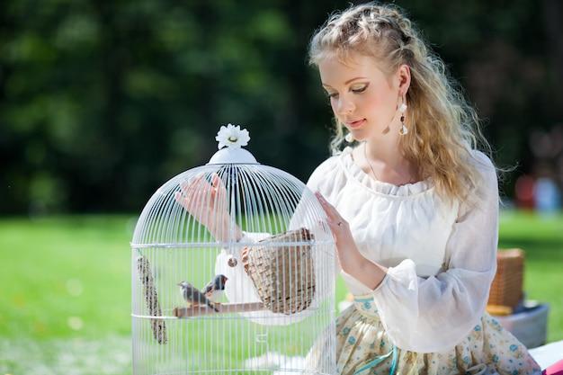 Леди, глядя на птиц в клетке.