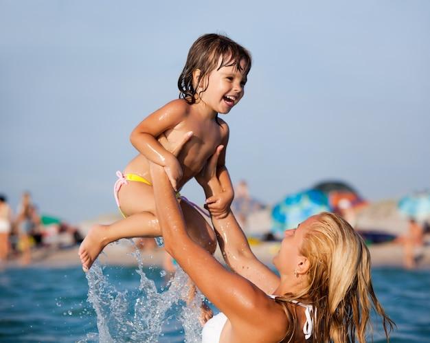 水に立って、小さな娘と遊ぶ若い母親