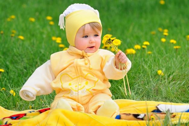 Милый ребенок сидит в травянистых местах с одуванчиками