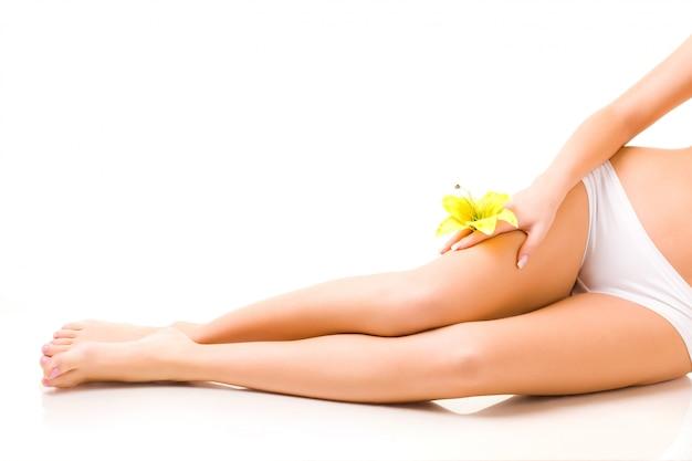 花を持つ少女の美しく手入れされた脚