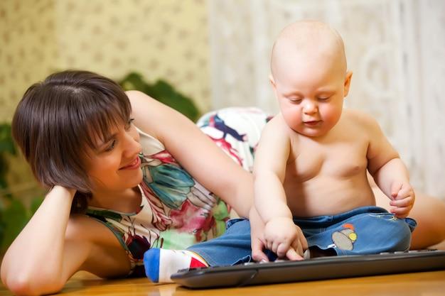 Мама с ребенком играет с клавиатурой на полу