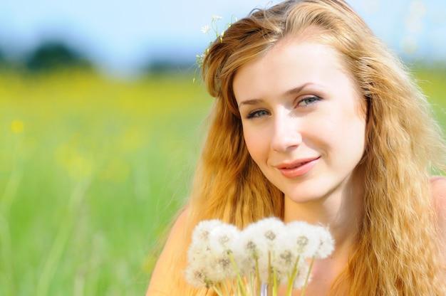 Портрет молодой девушки с одуванчиками в руках