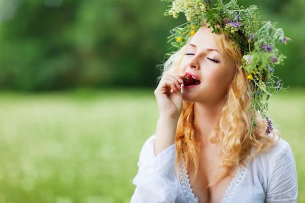 白いドレスとフローラルリース立って、夏の日にイチゴを食べる若い美しいブロンドの女性