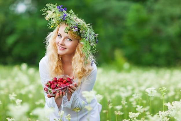 白いドレスと夏の日に新鮮なイチゴのボックスを保持しているフローラルリースの若い美しいブロンド女性