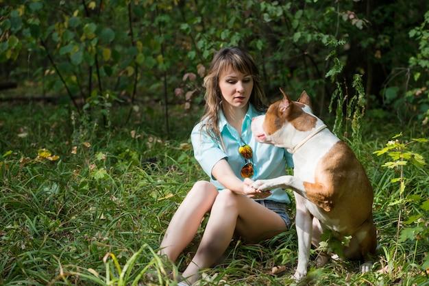 Красивая женщина, сидя на траве с собакой питбуль.
